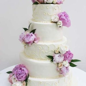 6 tiered cream wedding cake with purple flowers