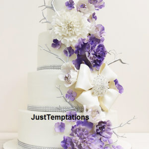 white 4 tiered cake with purple flower and twigs