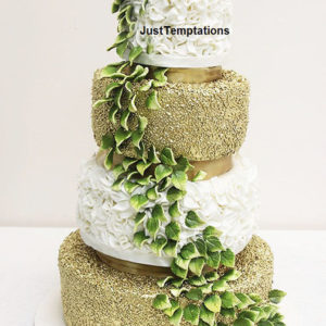gold confetti and white floral wedding cake
