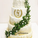 gold and white wedding cake with leaves