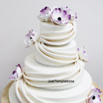 white wedding cake with prurple flowers