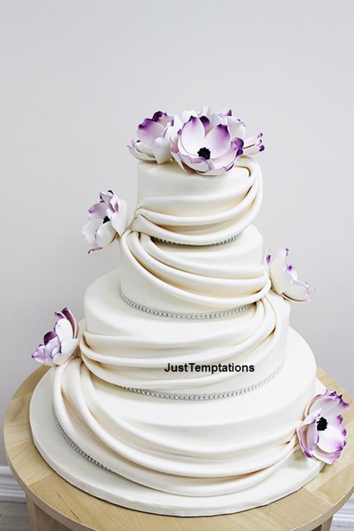 white wedding cake with prurple flowers