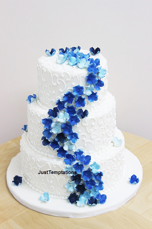 3 tiered white wedding cake with blue flowers