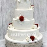 4 tiered white wedding cake with flowers