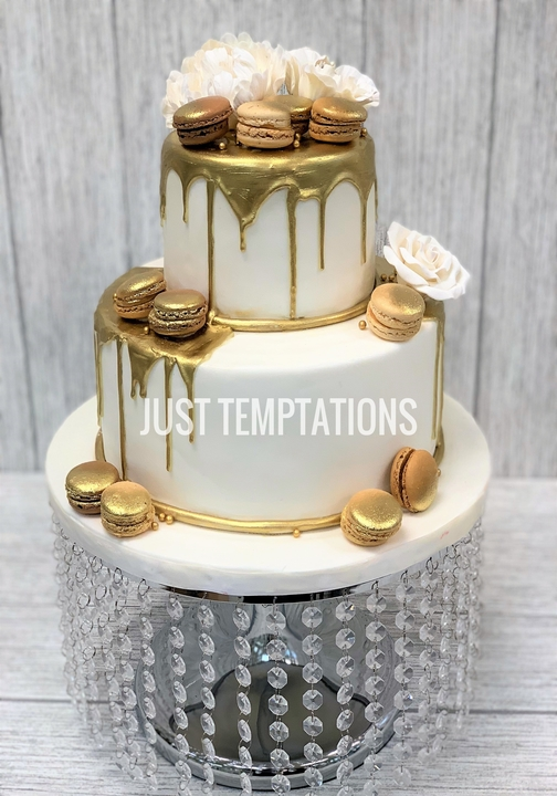 white and gold wedding cake with macaroons